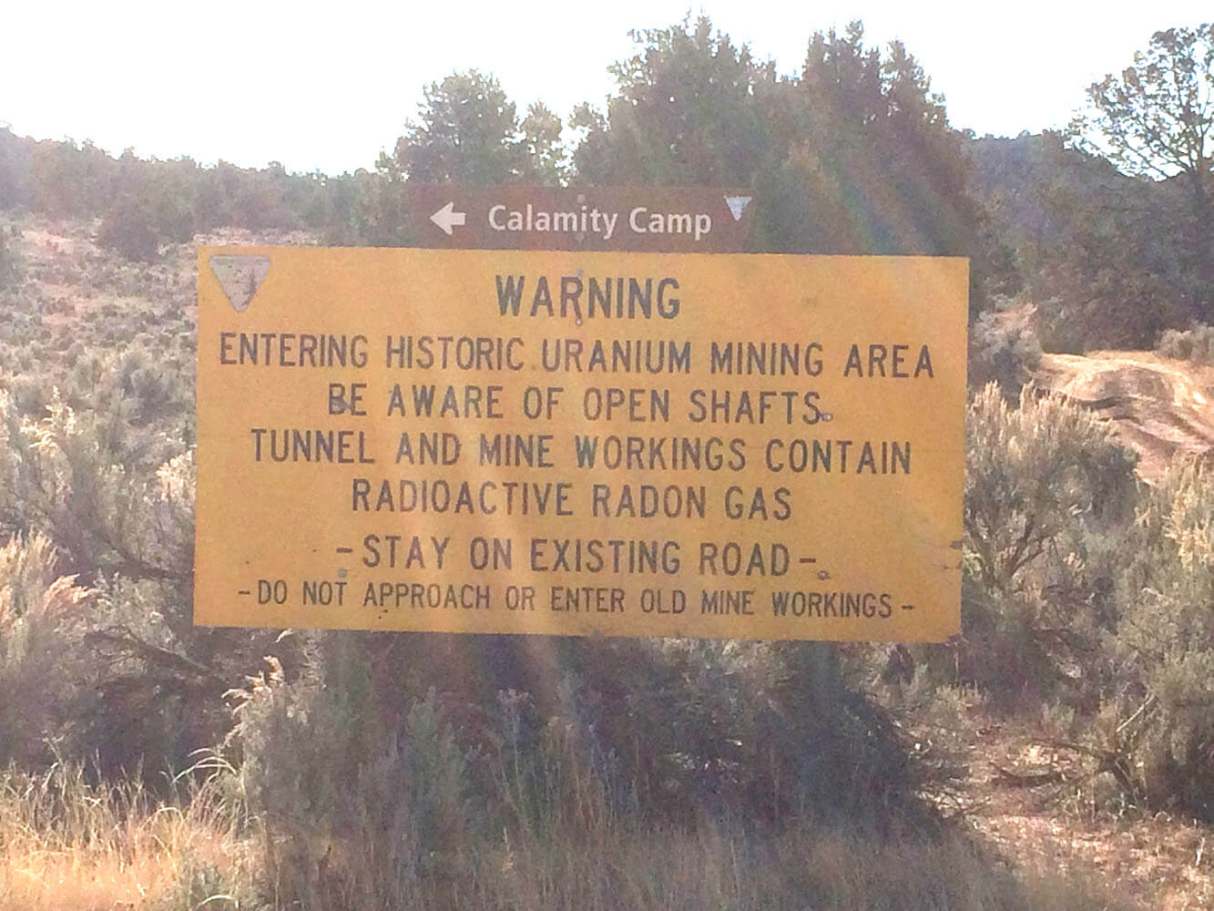 A warning sign as you enter the Calamity Camp reminds visitors of the potential hazards still present around the camp.